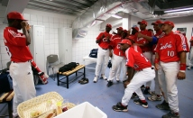 ATHENS - AUGUST 25: The gold medal winning team of Cuba celebrates by taking a team picture in the locker room after defeating Australia in the gold medal baseball game on August 25, 2004 during the Athens 2004 Summer Olympic Games at the Baseball Centre in the Helliniko Olympic Complex in Athens, Greece. (Photo by Donald Miralle/Getty Images)